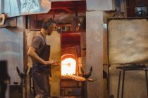 Glassblower heating glass in glassblowers oven at glassblowing factory — Stock Photo