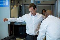 Flughafensicherheitsbeamter kontrolliert mit einem Metalldetektor einen Pendler am Flughafen — Stockfoto