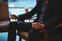 Средняя секция бизнесмена с использованием мобильного телефона и цифрового планшета в кафе — стоковое фото