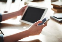 Ejecutivo empresarial que utiliza tableta digital y teléfono móvil en la oficina - foto de stock