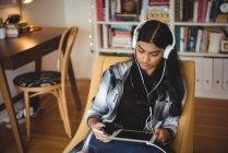 Femme écoutant de la musique avec écouteurs et tablette numérique dans le salon à la maison — Photo de stock