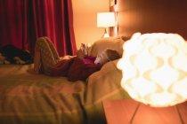 Fille en utilisant une tablette numérique tout en se relaxant sur le lit à la maison — Photo de stock
