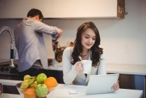 Woman using digital tablet while man working in background at kitchen — Stock Photo