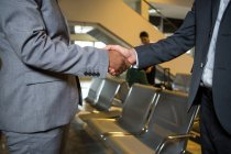 Business people shaking hands in airport terminal — Stock Photo