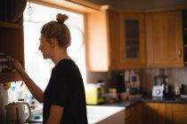 Mulher tirando caneca de café do armário da cozinha em casa — Fotografia de Stock