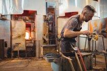 Стеклодув, формирующий расплавленное стекло на стекольном заводе — стоковое фото