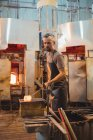 Glassblower shaping a molten glass on marver table at glassblowing factory — Stock Photo