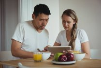 Couple using digital tablet while having breakfast at home — Stock Photo