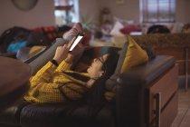 Красива жінка лежить і на дому за допомогою мобільного телефону — стокове фото