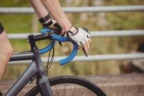 Gros plan de l'athlète à vélo sur la route — Photo de stock