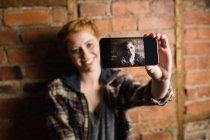 Mujer de pie contra la pared de ladrillo y tomando una selfie en su teléfono móvil - foto de stock