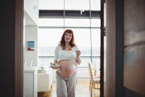Portrait of pregnant woman having salad in kitchen at home — Stock Photo