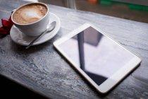 Капучино та цифрова табличка на стіл в кафе — стокове фото