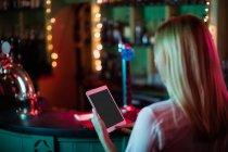 Vista posteriore della cameriera utilizzando un tablet digitale nella barra — Foto stock