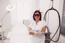 Врач в защитных очках стоит со скрещенными руками в клинике — стоковое фото