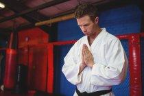 Каратист в молитвенной позе в фитнес-студии — стоковое фото