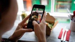 Femme cliquant sur une photo de salade à partir d'un téléphone portable dans le café — Photo de stock