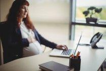 Femme d'affaires enceinte toucher le ventre tout en utilisant un ordinateur portable au bureau — Photo de stock