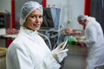 Портрет женщины-мясника с цифровыми планшетами на мясокомбинате — стоковое фото