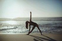 Женщина, занимающаяся йогой на пляже в сумерках — стоковое фото