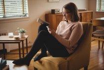 Femme assise sur une chaise en utilisant un téléphone portable et une tablette numérique dans le salon — Photo de stock