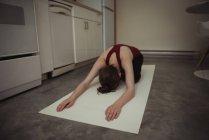 Mulher realizando ioga na cozinha em casa — Fotografia de Stock