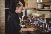 Waitress wiping espresso machine with napkin in cafe — Stock Photo