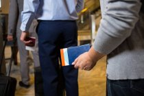Mid section of passengers standing with boarding pass in queue in airport — Stock Photo