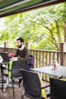 Man using laptop in bar terrace — Stock Photo