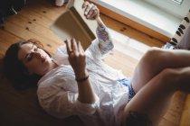 Женщина лежит на полу и читает книгу дома — стоковое фото
