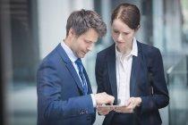Uomo d'affari e collega discutono su tablet digitale all'interno di un edificio per uffici — Foto stock