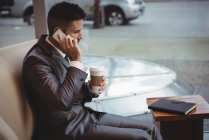 Businessman holding coffee while talking on mobile phone in the office premises — Stock Photo