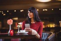 Donna in possesso di telefono cellulare nel ristorante — Foto stock