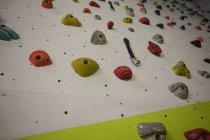 Pared de escalada artificial en el gimnasio para la práctica - foto de stock