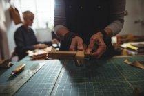 Средняя часть ремесленницы готовит кожаный ремень — стоковое фото