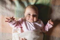 Крупный план милого улыбающегося ребенка, лежащего на кровати в спальне дома — стоковое фото