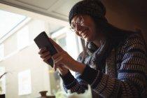 Femme souriante, à l'aide de téléphone portable près de fenêtre au café — Photo de stock