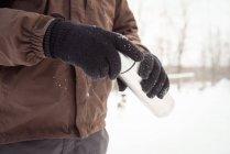 Sezione intermedia di musher holding thermos durante l'inverno — Foto stock