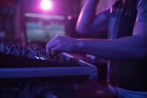 Mid section of male dj mixing music on mixing console in bar — Stock Photo