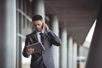Businessman using digital tablet while talking on mobile phone in the office campus — Stock Photo