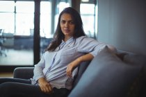 Portrait of businesswoman sitting on sofa in office — Stock Photo