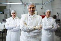 Bouchers debout avec les bras croisés dans l'usine de viande — Photo de stock