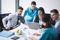 Команда врачей обсуждает за ноутбуком на совещании в конференц-зале — стоковое фото