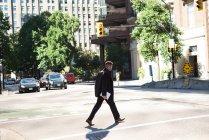 Uomo d'affari con tablet digitale che attraversa la strada alla luce del giorno — Foto stock