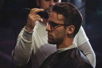 Homem recebendo cabelo aparado pelo estilista com aparador na barbearia — Fotografia de Stock