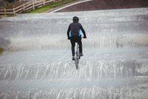 Vue arrière du cycliste à vélo BMX dans le skatepark — Photo de stock