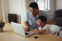 Padre e hijo usando teléfono móvil y portátil en la sala de estar en casa - foto de stock