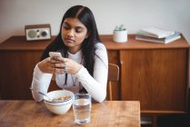 Woman using mobile phone while having breakfast in living room at home — Stock Photo