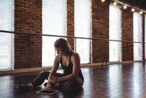Танцовщица с помощью мобильного телефона и планшета в танцевальной студии — стоковое фото