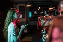 Beautiful woman using mobile phone at counter in bar — Stock Photo